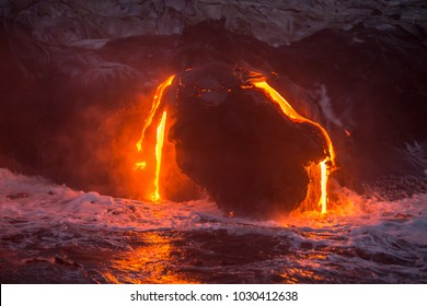 The active lava flow on the Big Island of Hawaii flowing hot magma from the volcano into the ocean during sunrise