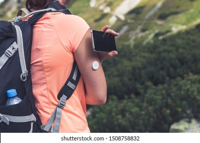 Active life of diabetics, woman hiking and checking glucose level with a remote sensor and mobile phone, new technology sensor checkup glucose levels without blood. Diabetes treatment.