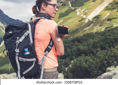 Active life of diabetics, woman hiking and checking glucose level with a remote sensor and mobile phone, new technology sensor checkup glucose levels without blood. Purple toned image.