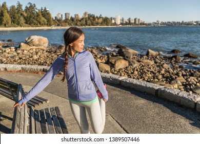 Active lifestyle Asian woman stretching before run in Stanley Park, Vancouver, Canada. Fit healthy city lifestyle people jogging fitness.