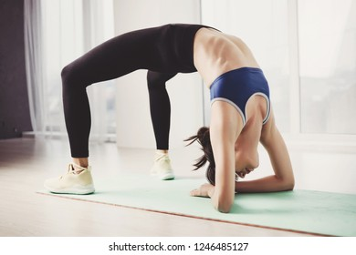 Active lifestyle, leisure, sport, fitness, yoga class, relaxation, balance, healthy spine, flexibility concept. Fit woman doing bridge plank exercise in yoga studio