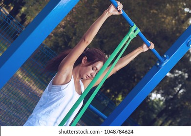 Active lifestyle. Slim brunette young woman training pull ups with resistance band in outdoors gym at sunny summer day.