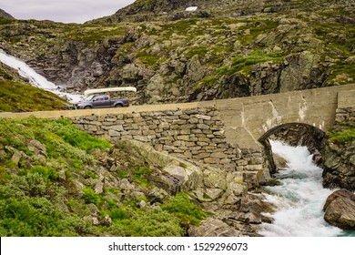 Active lifestyle sport. Car with canoe on top roof drive over river on national tourist scenic route Gamle Strynefjellsvegen, Southern Norway.