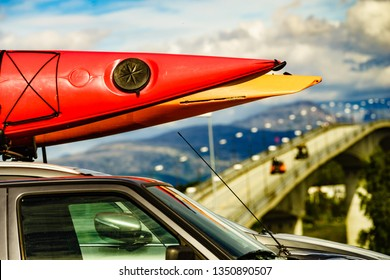 Active lifestyle sport concept. Car with canoes on top roof, bridge and mountains landscape in the background