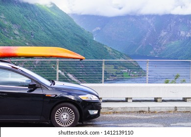 Active lifestyle sport concept. Car with canoe on top roof, Geiranger fjord landscape in background