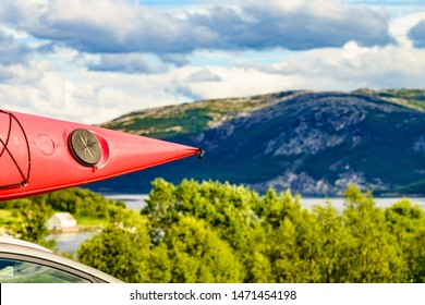 Active lifestyle sport concept. Car with red canoe on top roof, mountains landscape in the background