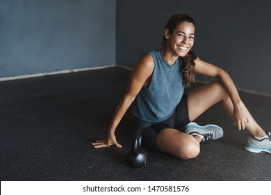 Active lifestyle and sport concept. Happy gorgeous fit sportswoman wear sportswear, motivated good training fitness session, rest on gym floor, workout kettlebell squats, smile camera pleased