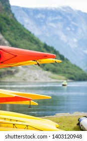 Active lifestyle sport concept. Many canoes outdoor in rental center, norwegian fjord landscape in the background
