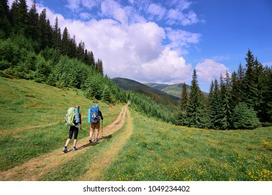 Active lifestyle. Traveling together. Couple of tourists with backpacks in the Carpathian mountains.