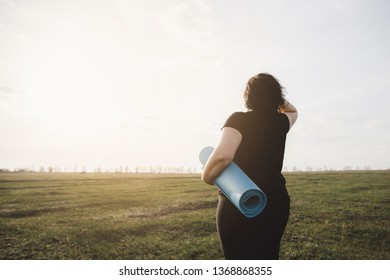 Active lifestyle, yoga, flexibility, sport, fitness, weight loss. Overweight woman with yoga mat before outdoor workout in nature