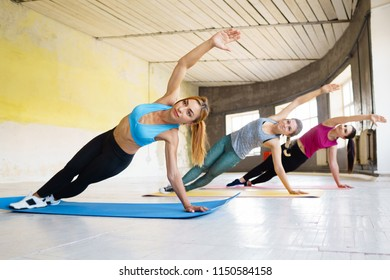 Active lifestyle, yoga trainer, flexibility, sport, fitness. Sporty women doing side plank on mats at group workout
