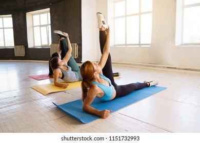 Active lifestyle, yoga trainer, flexibility, sport, fitness. Sporty women doing stretching exercises on mats at group workout