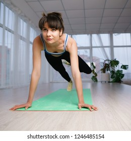 Active lifestyle, yoga trainer, flexibility, sport, fitness. Sporty woman doing complicated plank exercise on mat at yoga studio