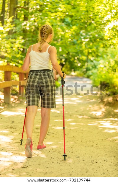 Active lifestyle. Young tourist woman back view hiking in forest pathway
