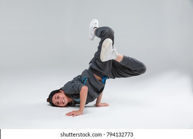 An active little boy dancing lying on chest resting arms, bending legs in lap. On a gray background.