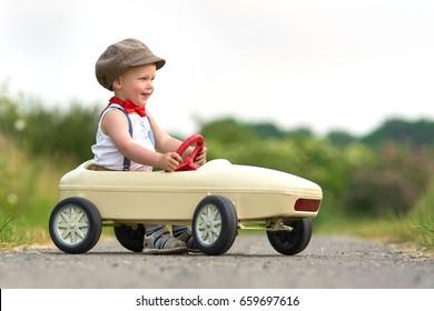 Active little boy driving pedal car in summer garden, outdoors.