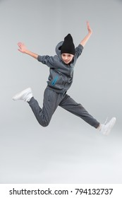 An active little boy jumping plunged legs clutching. On a gray background.