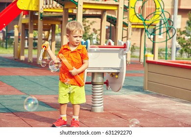 Active little boy on playground. child playing bubble blower