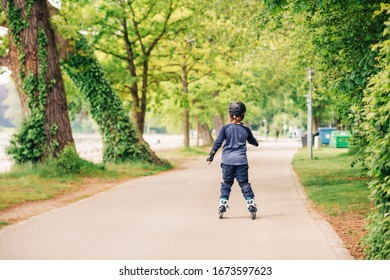 Active little boy skating in summer park, healthy lifestyle for children, back view