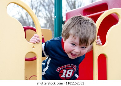an active little boy yells loudly from the top of a colorful slide at the playground