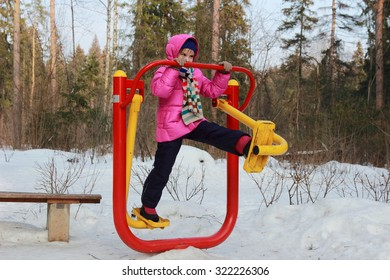 Active little girl at playground in winter outdoor Zelenograd, Moscow, Russia