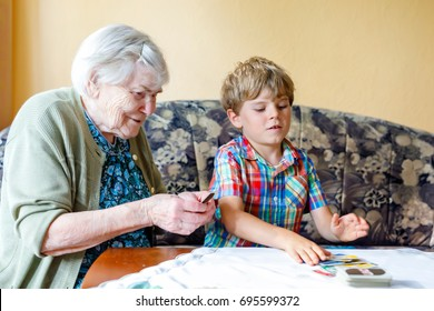 Active little preschool kid boy and grand grandmother playing card game together at home. little child and retired woman having fun. Happy family: grandchild and senior woman