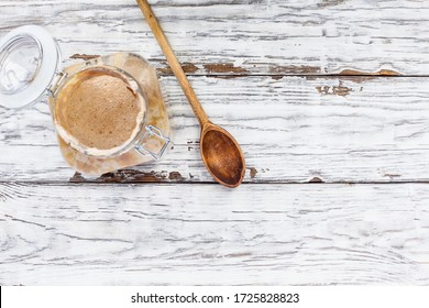 Active live whole wheat sourdough starter with a wooden spoon over a white rustic wood table / background with free space for text Image shot from overhead view.