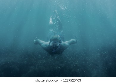 Active male freediver in mask swimming underwater, front view.