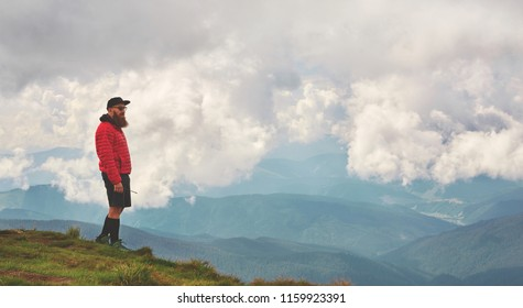 Active male hiker enjoying panoramic view of beautiful cloudy sky in mountains, travel and outdoor adventure concept. Carpathians, Ukraine
