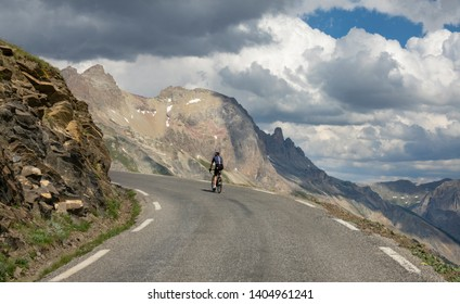 Active male tourist enjoys a scenic bicycle trip along the great alpine route on a cloudy day. Unrecognizable road cyclist rides a bike down an empty mountain road on a cloudy day in the French Alps.