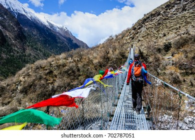 Active man backpacker crossing suspension bridge with buddhist prayer flags on the Langtang trek in Nepal.