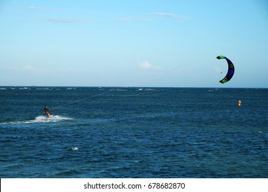 Active man enjoy summer with outdoor activity on Vietnam beach, kite surfing water sport, people on board and control kite with wind make jun for kite surfer
