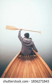 Active man enjoy winter canoe ride in the haze