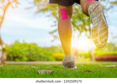 Active man healthy runner jogging outdoor in park morning with sunrise, Trail running. Muscle leg injury.