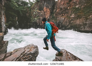 Active man jumping on rocks travel adventure active vacations healthy lifestyle extreme sports above canyon river