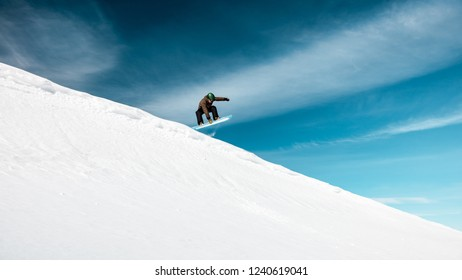 Active man on snowboard in snowy mountains over blue sky background, happy healthy lifestyle, extreme winter vacation
