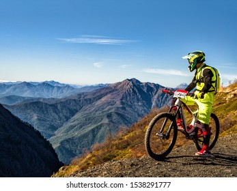 Active man riding downhill mountain bike and looking at mountains