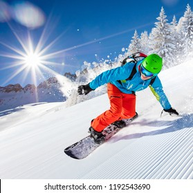 Active man snowboarder riding on slope during beautiful sunny day in the ountains.