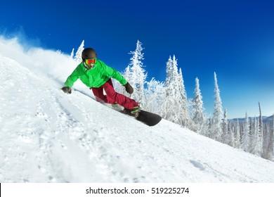 Active man snowboarder riding on slope. Snowboarding closeup. Sheregesh ski resort