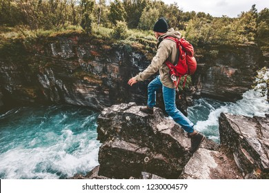 Active man trail running on rocks over river canyon hiking traveling lifestyle concept extreme journey vacations in Sweden wilderness
