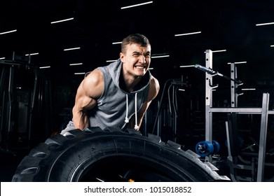 Active man work hard - flipping tire in crossfit training