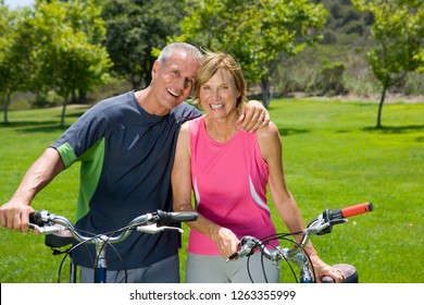 Active mature couple exercise by riding bikes in park at camera