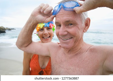 Active mature couple in swimming costumes on beach with goggles