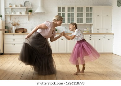 Active mature grandma dance with small granddaughter on warm floor at modern kitchen in puffy ballerina skirts. Joyful senior nanny play princesses with little girl dancing listen to music having fun