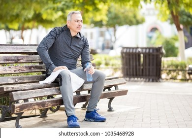 Active middle aged man resting on a park bench with a water bottle and towel after doing jogging outdoors