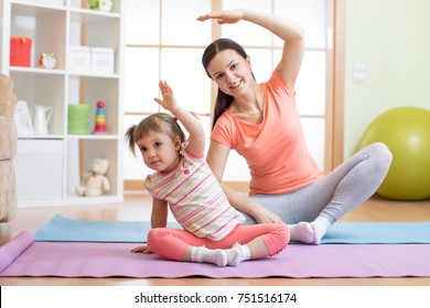 Active mom and child daughter are engaged in fitness, yoga, exercise at home