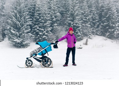 Active mother with baby stroller enjoying motherhood in winter forest, mountains landscape. Jogging or power walking woman with sledge pram in woods. Beautiful winter snowy inspirational mountains.