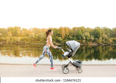 Active mother jogging. Jogging or power walking woman with pram at sunset. Mother with child in stroller running
