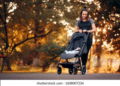 Active Mother Wearing Sporty Outfit Pushing Stroller in the Park. Fitness mom ready for postnatal body recovery and exercising