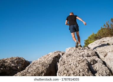Active mountain skyrunner dressed black t-shirt and running shoes jogging the cliff summit during the morning scamper. Sporty people activities a wide-angle concept back view image.